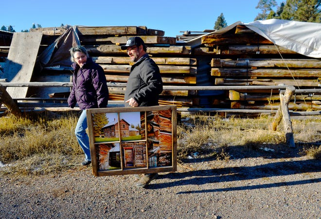 Erin Dey and Bill Frisbee walk by the stacked logs belonging to the Matt King historic log cabin, which the pair hope to reconstruct on the east end of Lincoln along Montana Highway 200. Frisbee carries a collection of photos of the cabin before it was deconstructed.