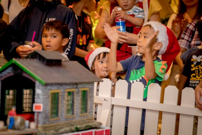 """Guests listen to Christmas Carols performed by Guam Symphony Sociey during the launching of Hilton Guam Resort and Spa's  """"Holiday Train"""" on Dec. 5."""