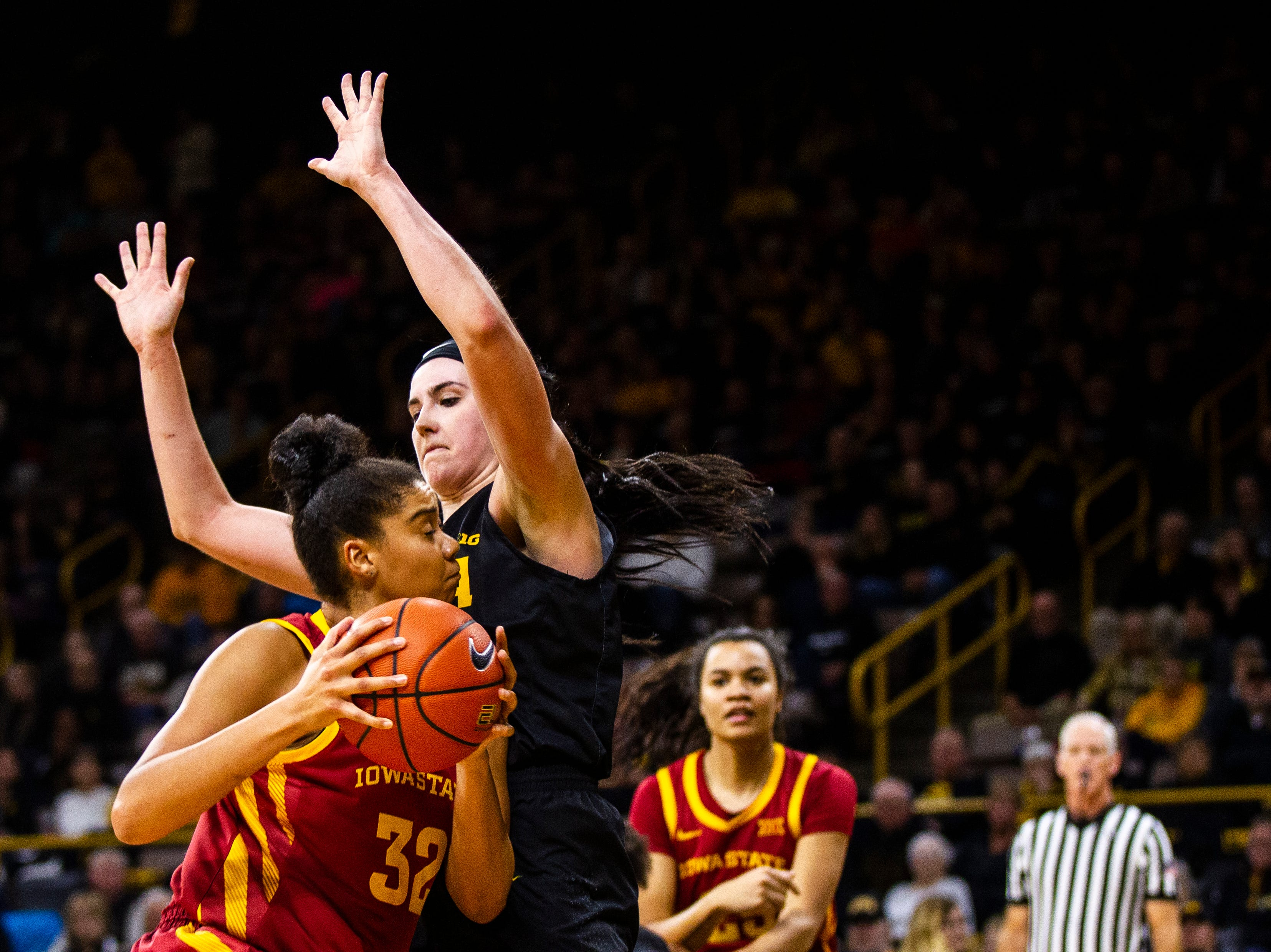 Iowa State forward Meredith Burkhall (32) gets defended by Iowa forward Megan Gustafson (10) in the paint during a Cy-Hawk series NCAA women's basketball game on Wednesday, Dec. 5, 2018, at Carver-Hawkeye Arena in Iowa City.