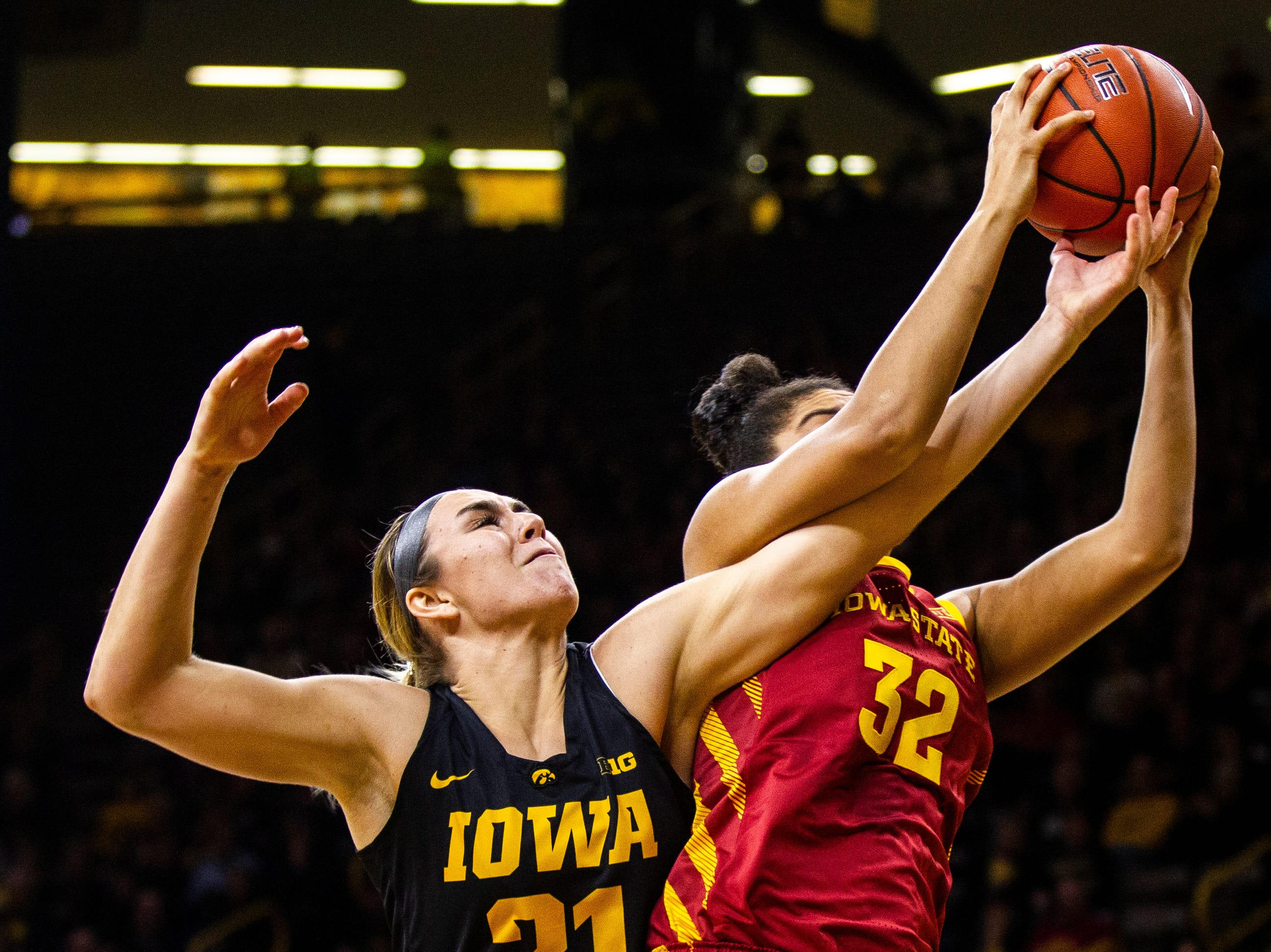 Iowa State guard Meredith Burkhall (32) battles Iowa forward Hannah Stewart (21) for a rebound during a Cy-Hawk series NCAA women's basketball game on Wednesday, Dec. 5, 2018, at Carver-Hawkeye Arena in Iowa City.