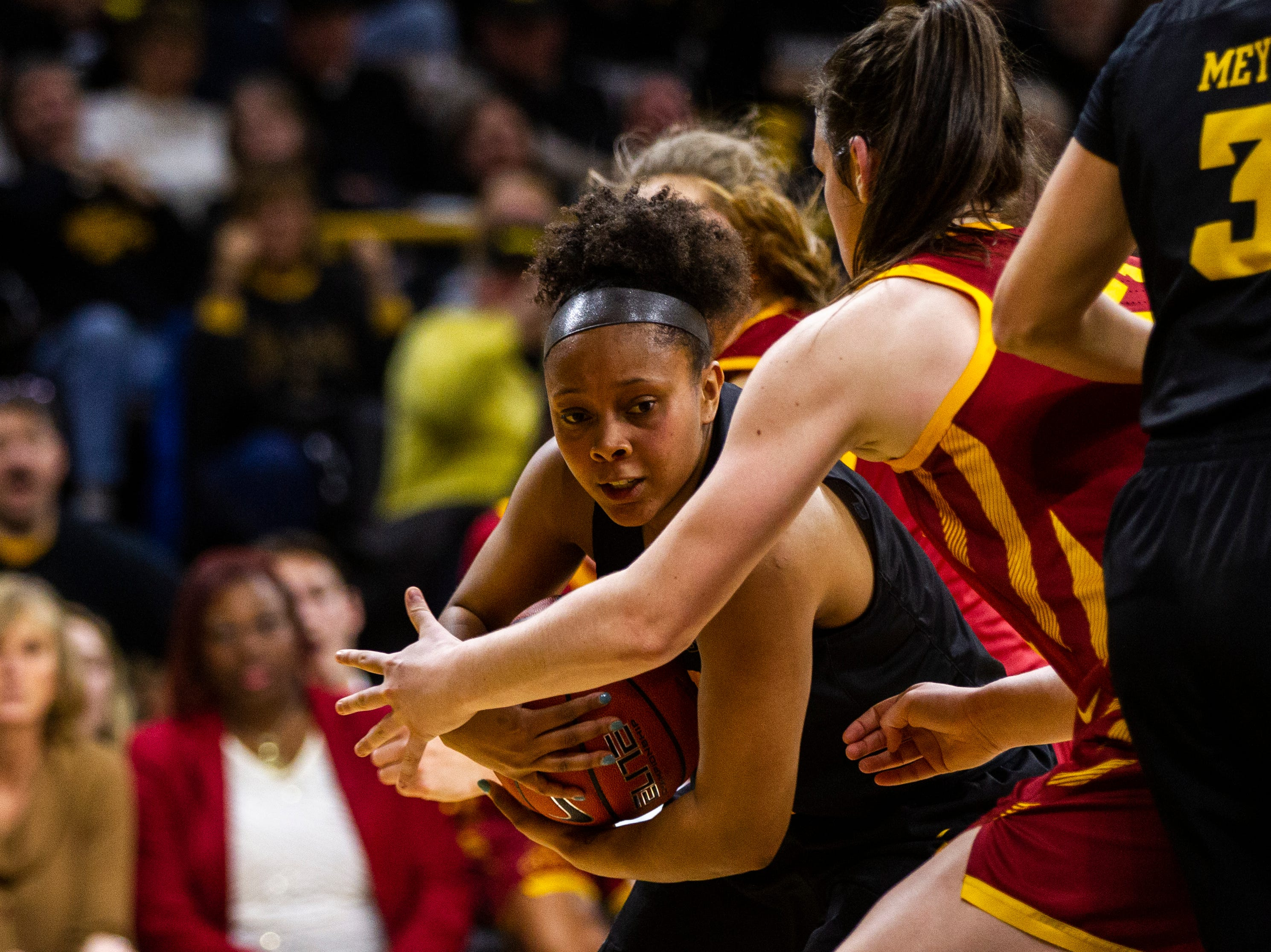 Iowa guard Tania Davis (11) gets defended in the paint by Iowa State guard Bridget Carleton (21) during a Cy-Hawk series NCAA women's basketball game on Wednesday, Dec. 5, 2018, at Carver-Hawkeye Arena in Iowa City.