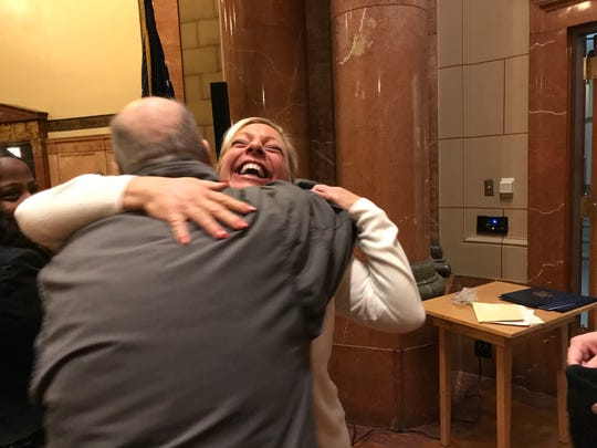 Rebecca Mills accepts a congratulatory hug after she delivered the keynote speech at the Indianapolis Veterans Court's graduation ceremony at the Indiana War Memorial, Nov. 30, 2018.