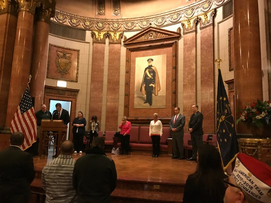 Rebecca Mills, center in white, on the Indiana War Memorial stage to deliver the keynote speech at the Indianapolis Veterans Court's graduation ceremony, Nov. 30, 2018.