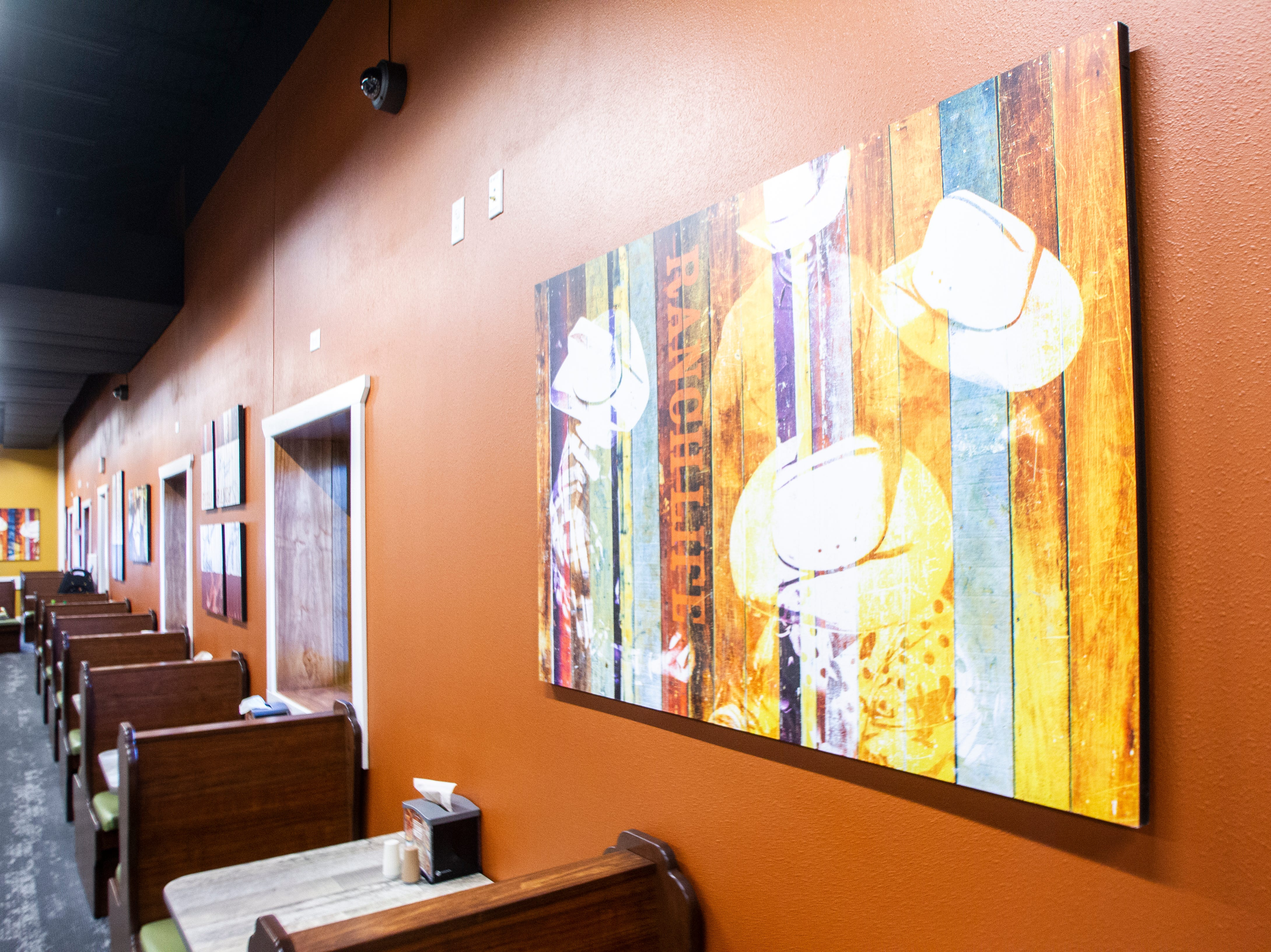Wall art hangs above booths for two during a soft opening event on Thursday, Dec. 6, 2018, at Pizza Ranch on Highway 1 West in Iowa City.