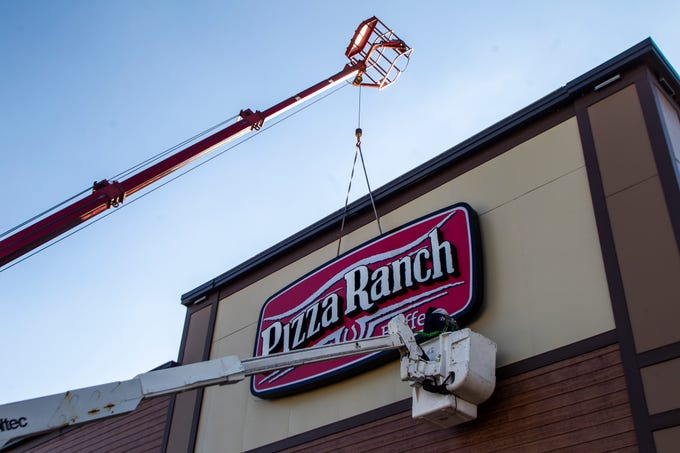 A sign is rigged into place during a soft opening event on Thursday, Dec. 6, 2018, at Pizza Ranch on Highway 1 West in Iowa City.