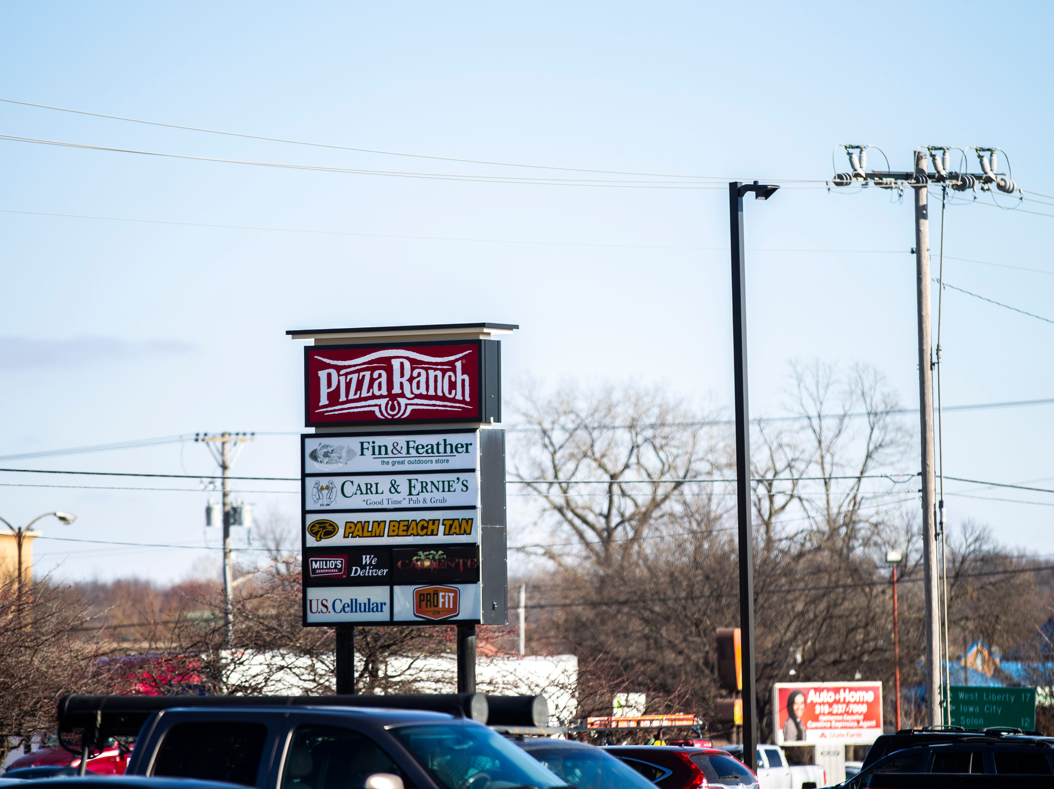 Businesses' logos are displayed on a sign in the parking lot during a soft opening event on Thursday, Dec. 6, 2018, at Pizza Ranch on Highway 1 West in Iowa City.