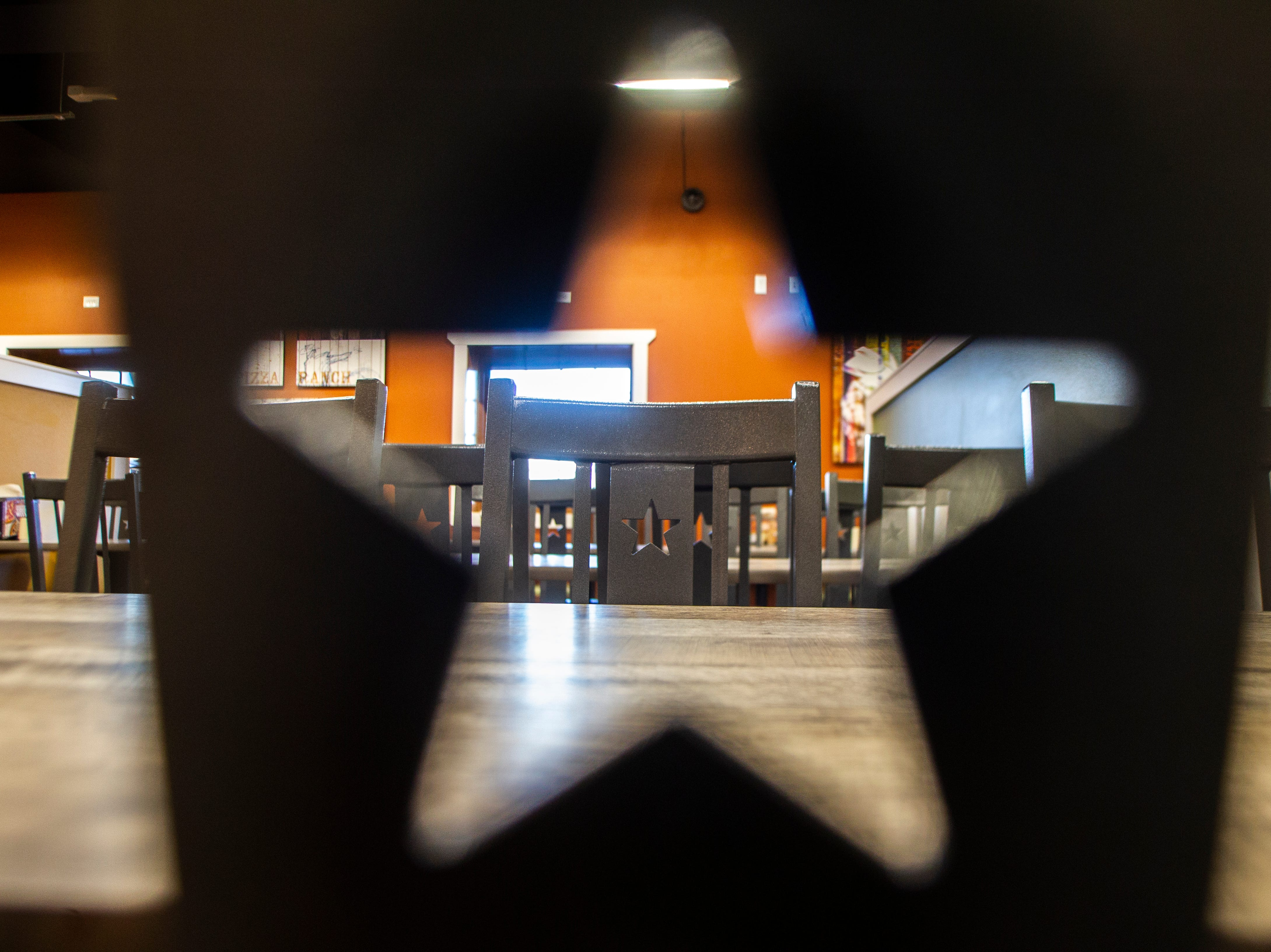A star-shaped cutout is seen through a chair during a soft opening event on Thursday, Dec. 6, 2018, at Pizza Ranch on Highway 1 West in Iowa City.