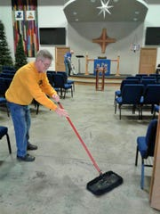 Justin Collier sweeps in the church sanctuary, while Clayton Ludvigson prepares to vacuum the alter.  Nine retired volunteers clean the church every Monday morning.