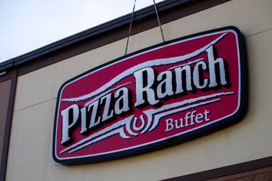 A crew works to install a backlit sign outside during a soft opening event on Thursday, Dec. 6, 2018, at Pizza Ranch on Highway 1 West in Iowa City.