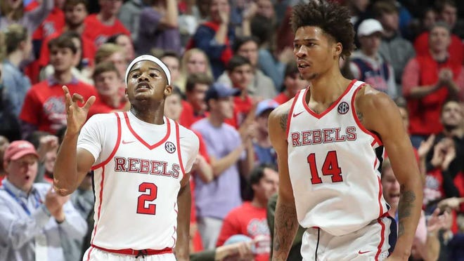 Ole Miss basketball players Devontae Shuler (2) and KJ Buffen (14) discuss a play on the court.