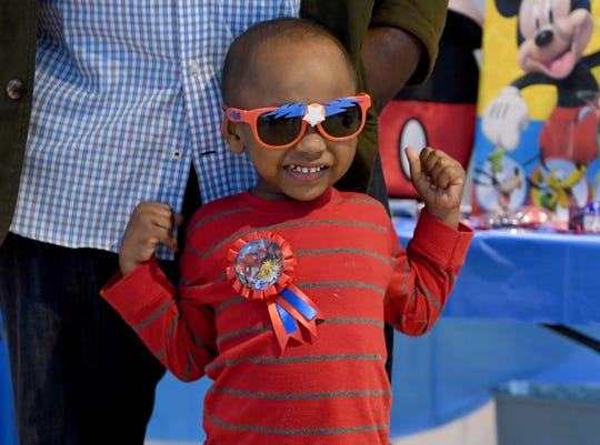 3-year-old Kyler Bond flexes his muscles after Make-A-Wish Foundation granted his wish to go to Disney World during a presentation at Robinson Toyota, Thursday, December 6.