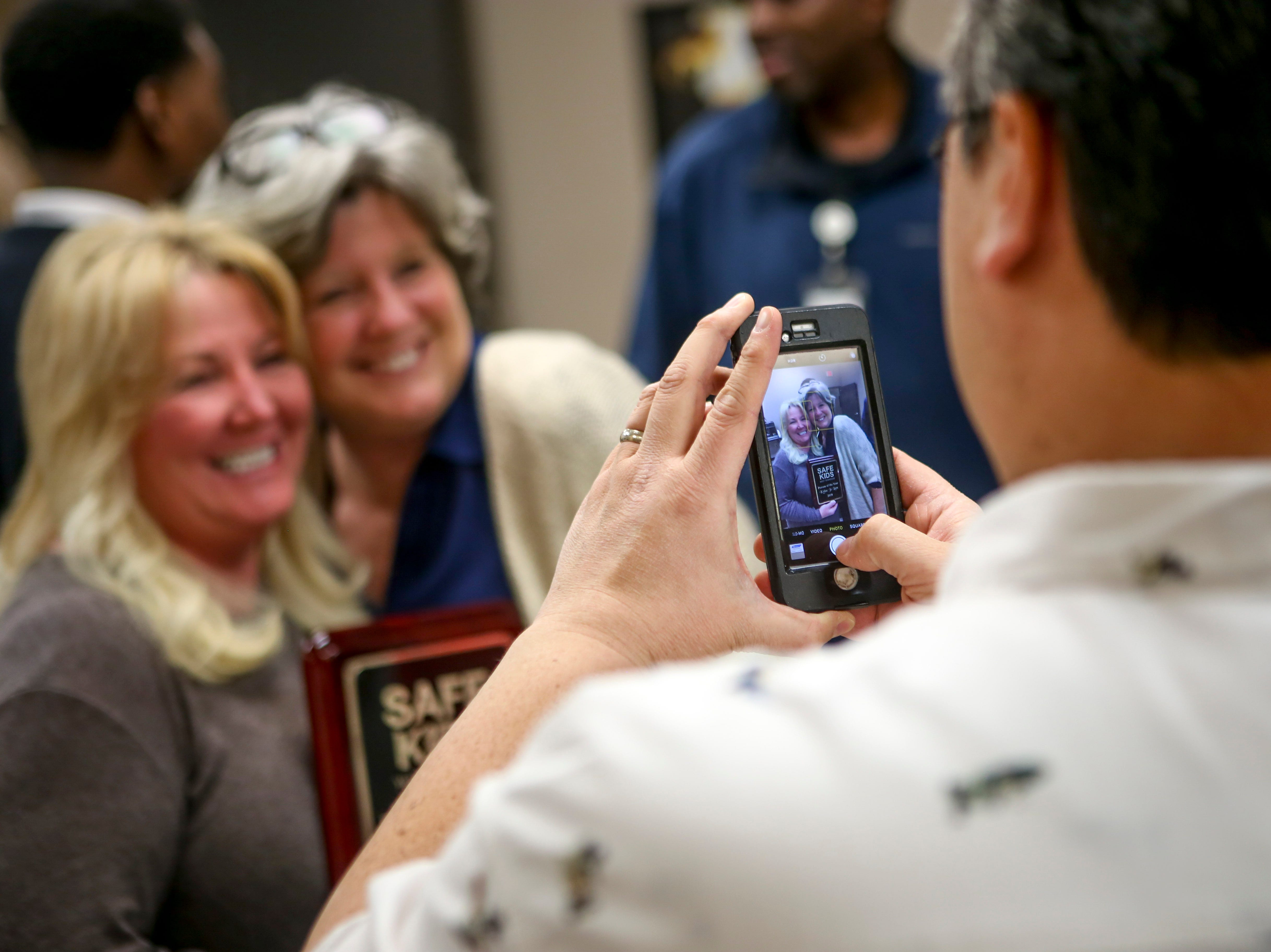 Kylee Jo Lam embraces Diane Rushing for a photo taken by Lam's husband Michael Lam MD after being presented the Safe Kids Person of the Year award at Madison County Fire Department in Jackson, Tenn., on Thursday, Dec. 6, 2018.