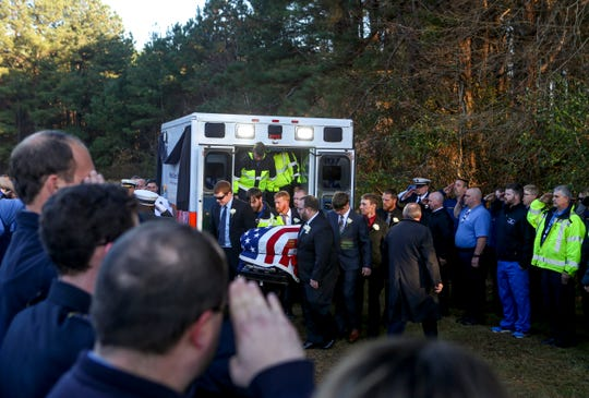 Family and friends bring the body of Zach Pruitt out from the ambulance and walk it to the funeral location while attendees salute and pay their respects at Highland Memorial Gardens in Jackson, Tenn., on Wednesday, Dec. 5, 2018.