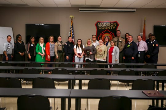 Attendees at the presentation of the Safe Kids Person of the Year award stand around Kylee Jo Lam, who was presented the award, at Madison County Fire Department in Jackson, Tenn., on Thursday, Dec. 6, 2018.