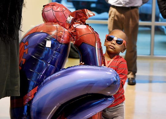 3-year-old Kyler Bond carries his Spiderman balloon at Robinson Toyota afterafter Make-A-Wish Foundation granted his wish to go to Disney World, Thursday, December 6.