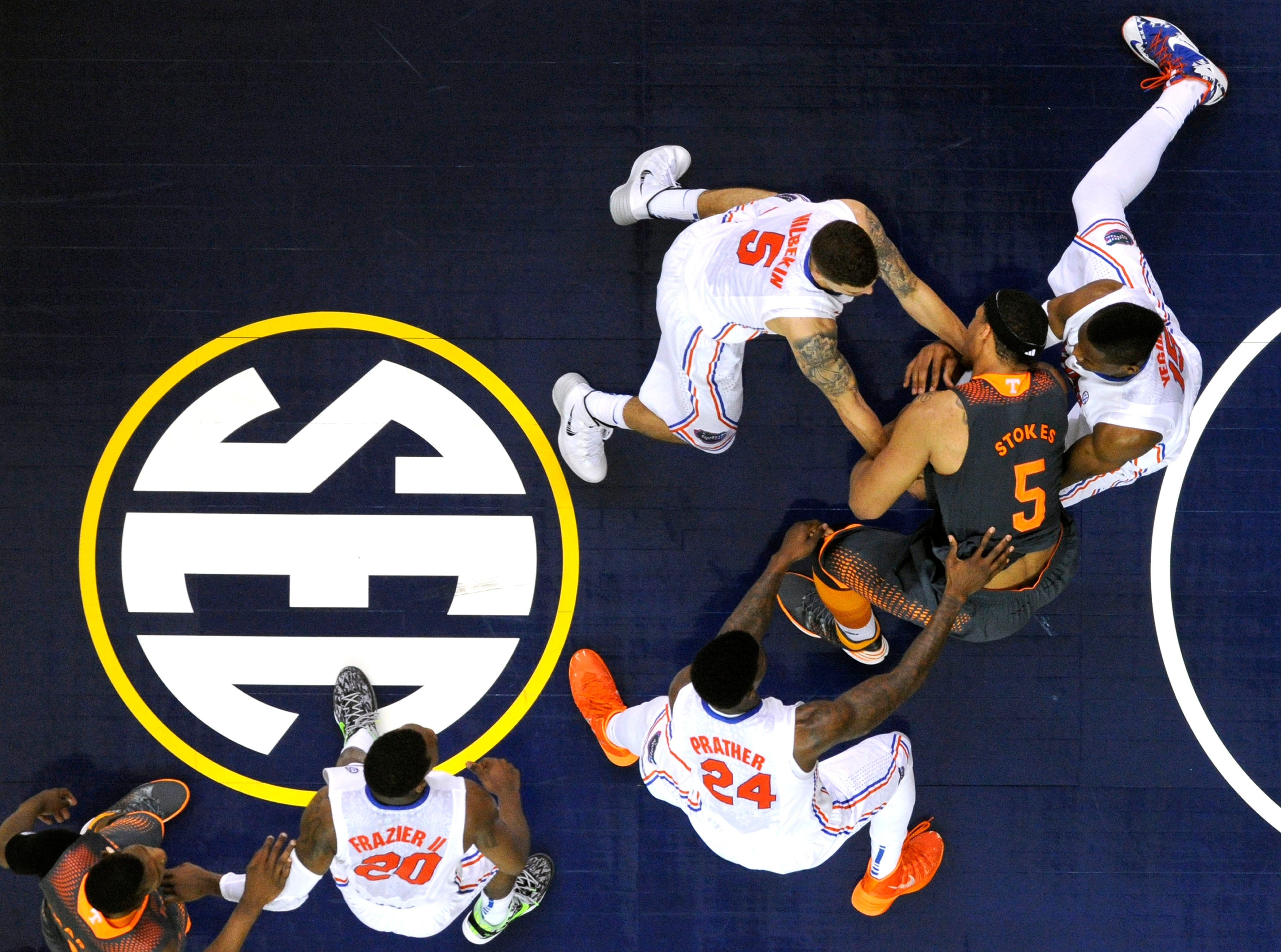 Florida forward Casey Prather (24), Florida guard Scottie Wilbekin (5), and Florida forward Will Yeguete (15) swarm Tennessee forward Jarnell Stokes (5) during the second half of an SEC tournament semifinal game at the Georgia Dome in Atlanta on Saturday, March 15, 2014. Tennessee lost 56-49.