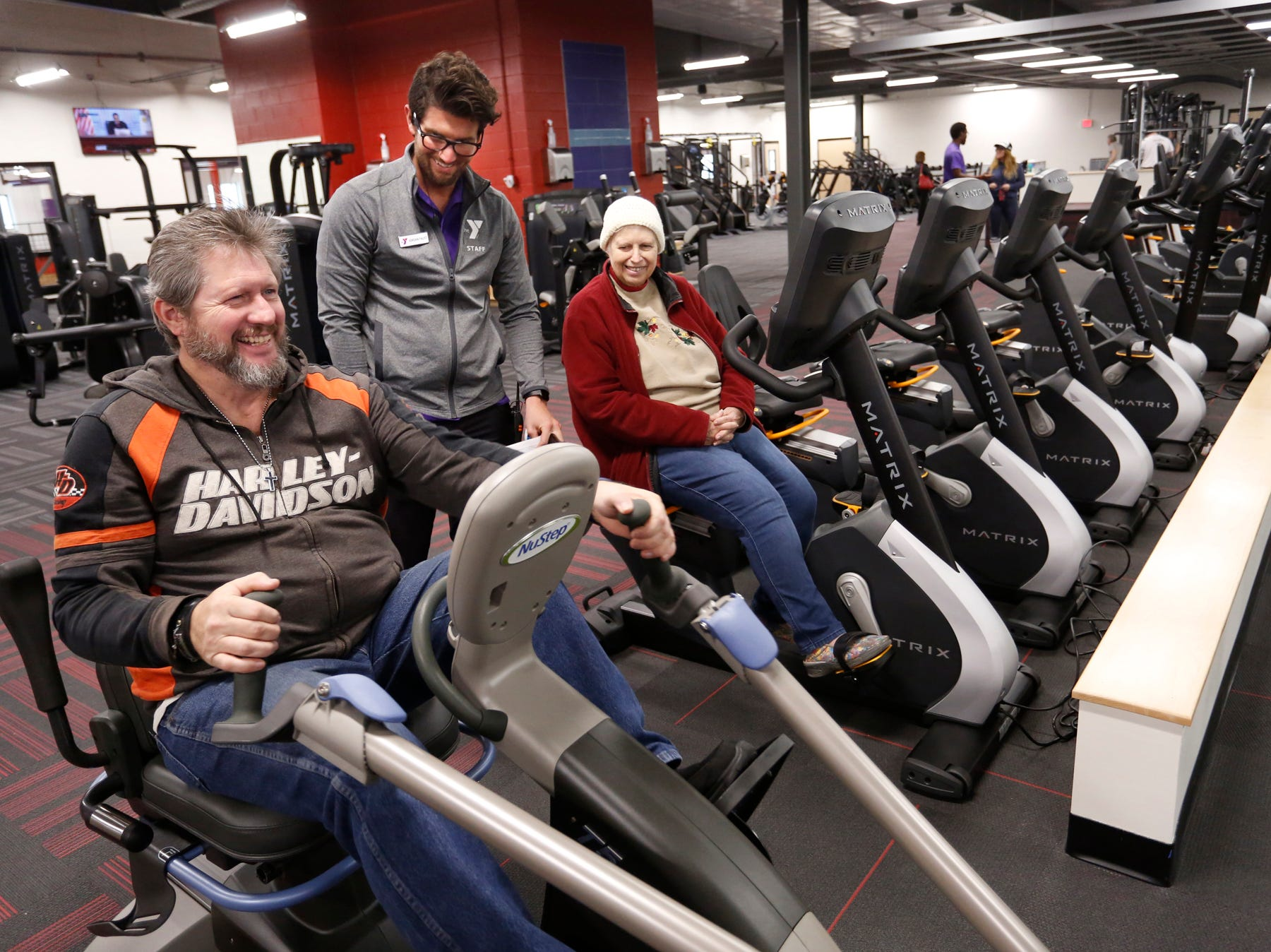 Jordan Faust, center, introduces Rick and Barbara Fields to the NuStep rehab bike and the Matrix Bike in the James and Cari Gothard Wellness Center Thursday, December 6, 2018, at the new Lafayette Family YMCA, 3001 S. Creasy Lane in Lafayette. The facility celebrated its grand opening Thursday.