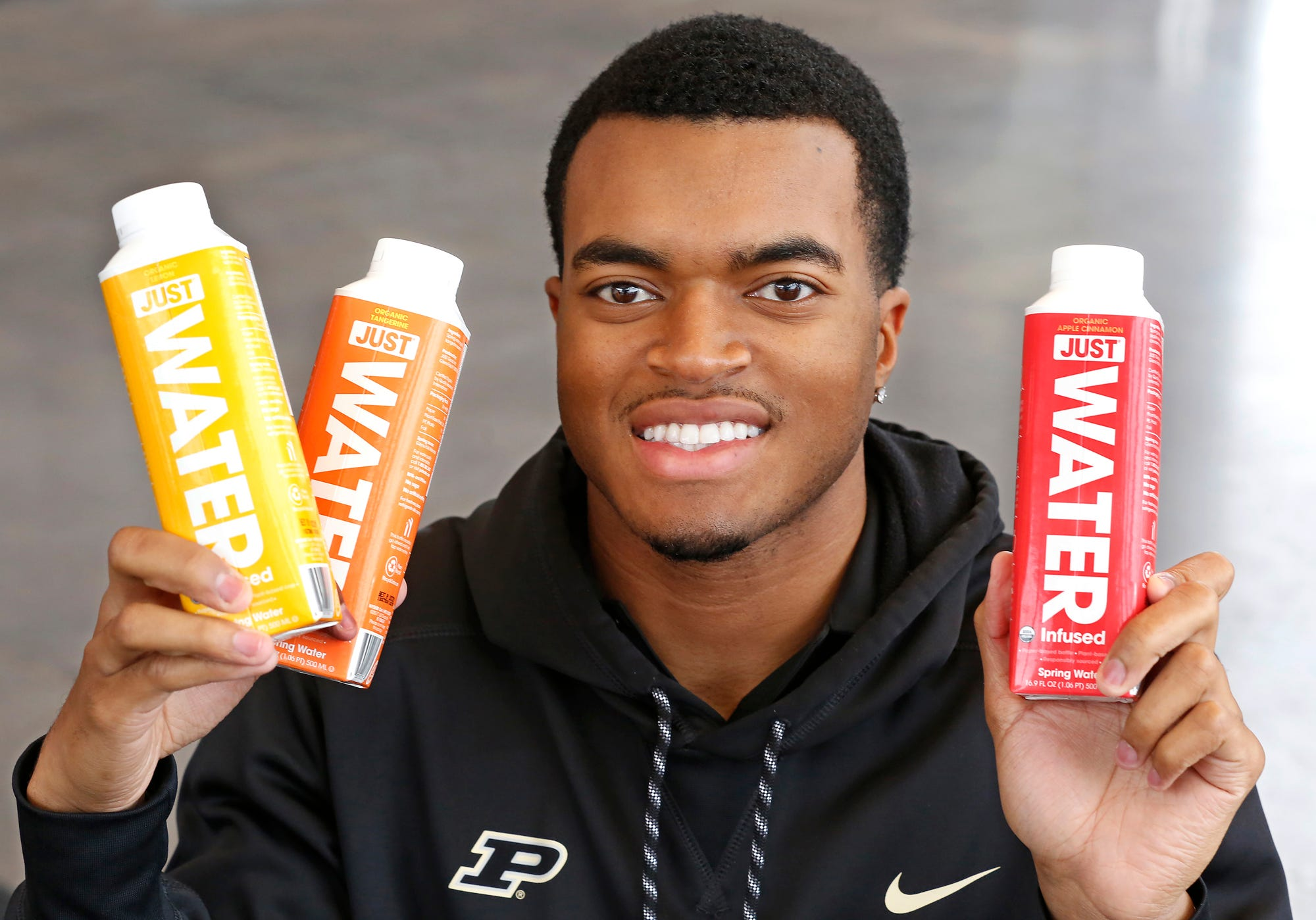 Aaron Banks with bottles of Just Water Thursday, December 6, 2018, on the campus of Purdue University. Banks, who is Purdue student body president and also a quarterback on the football team, negotiated the deal to bring Just Water, featuring environmentally friendly packaging, to the Purdue campus.