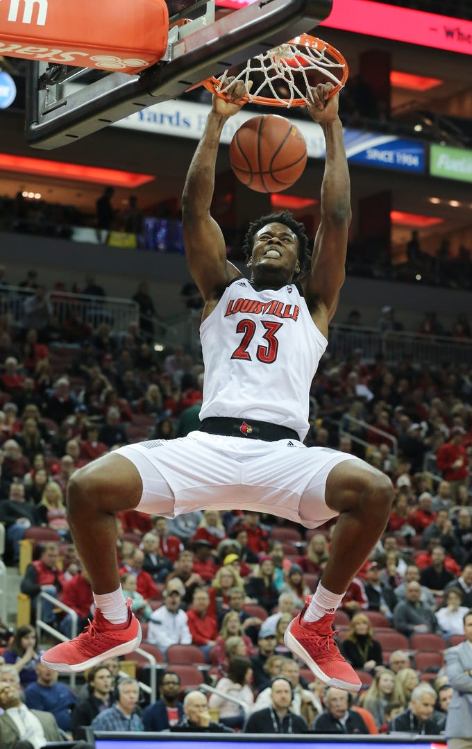 Louisville's Steven Enoch (23) slammed in two of his 14  first half points against Central Arkansas during their game at the Yum Center.   Dec. 5, 2018