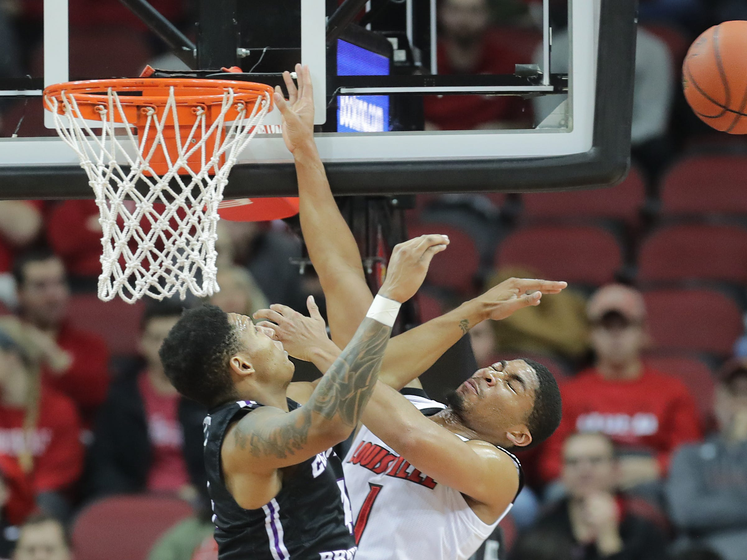 Louisville's Christen Cunningham gets fouled by Central Arkansas' Khaleem Bennett. 