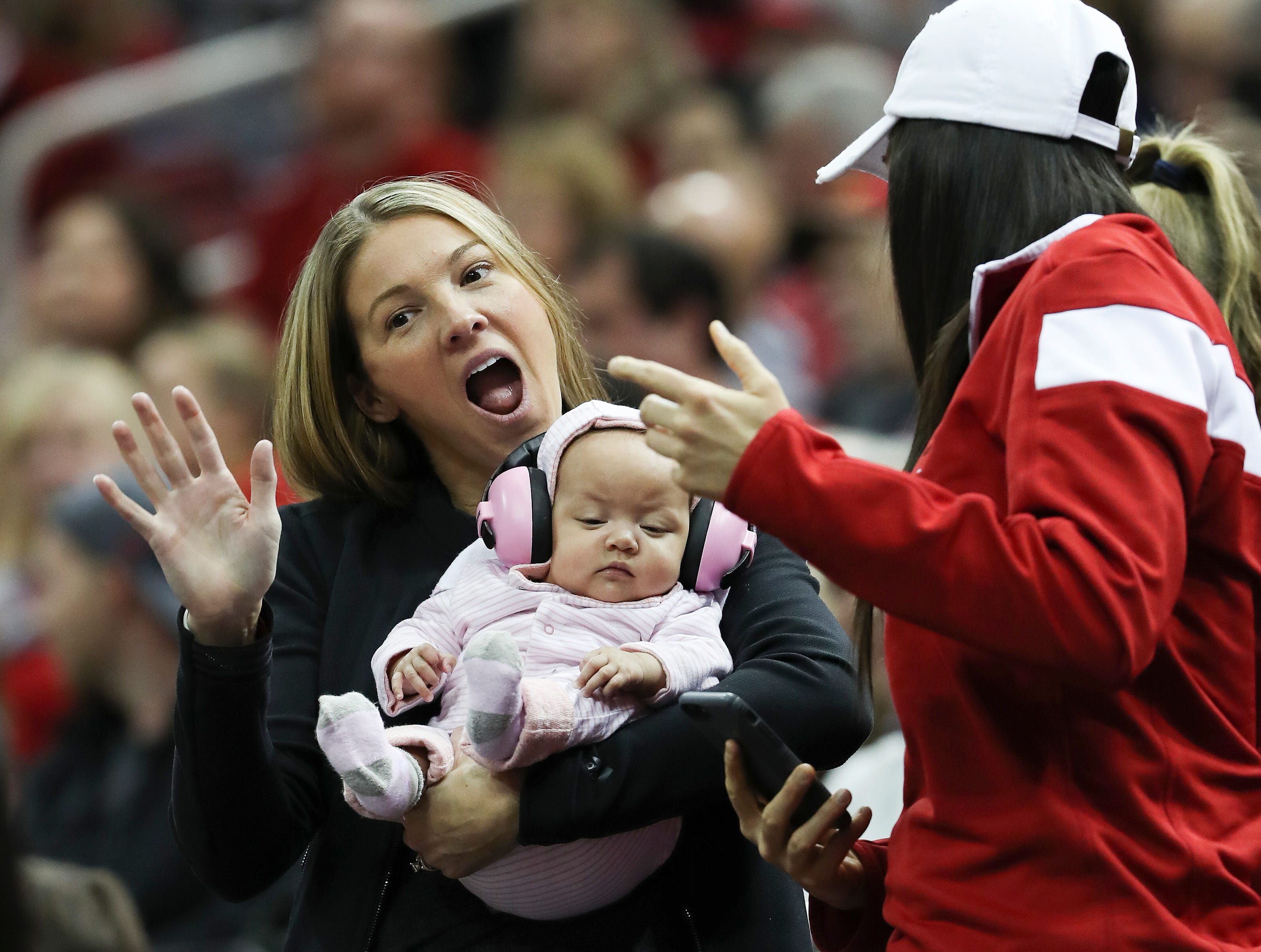 Christi Mack, wife of Louisville's head coach Chris Mack, held a baby during the Central Arkansas game at the Yum Center.  