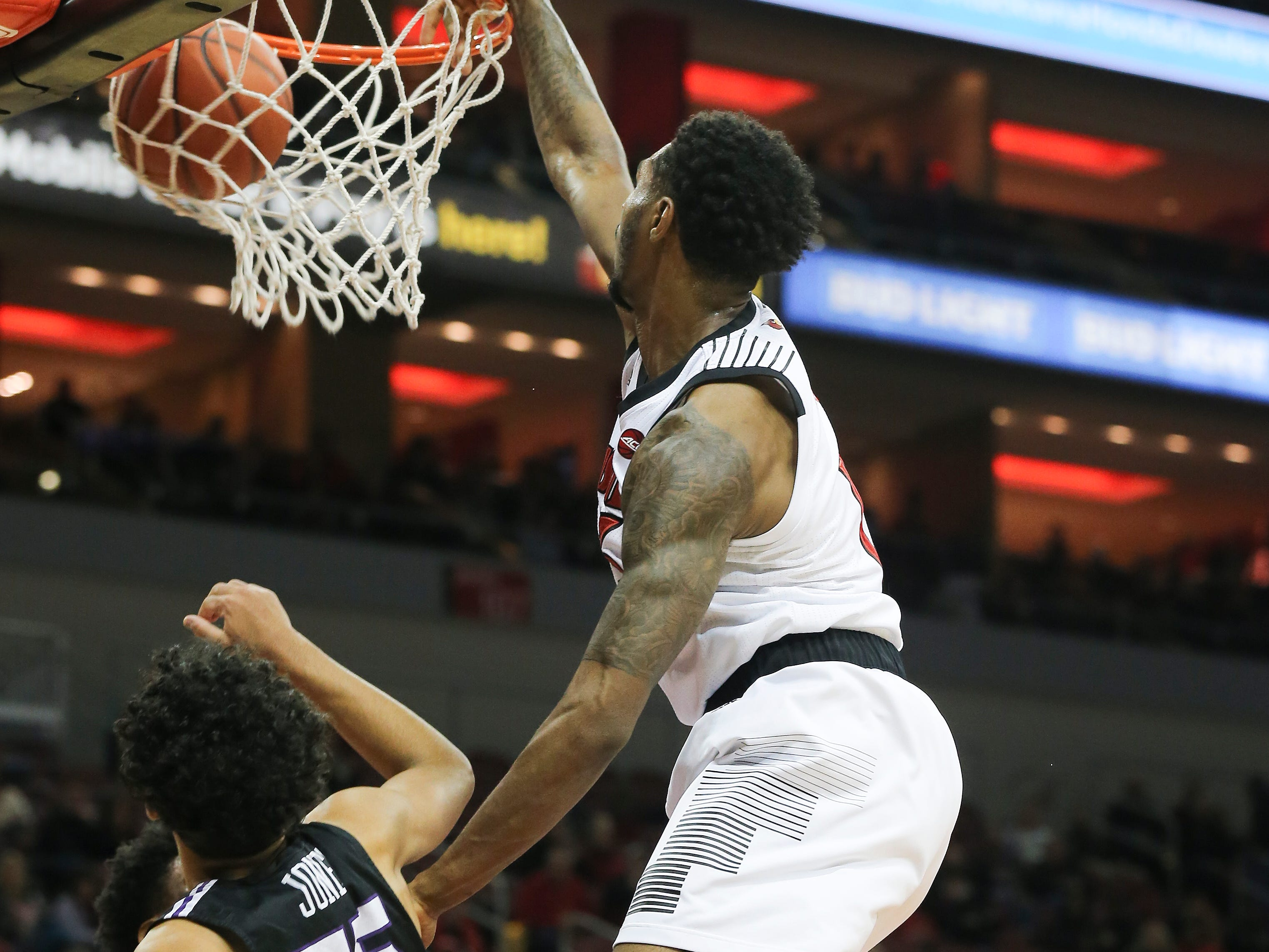 Louisville's V.J. King (13) slams in a put back dunk against Central Arkansas' DeAndre Jones (55) during their game at the Yum Center.  