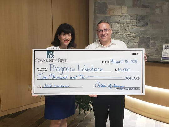 Community First Credit Union gives a donation to Progress Lakeshore.