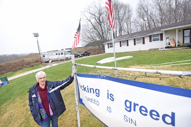 Ann Robinson stands in front of her home near Perrysville with an anti-fracking sign. Behind Robinson, a large mound can be seen at the adjacent property where a well is being installed.