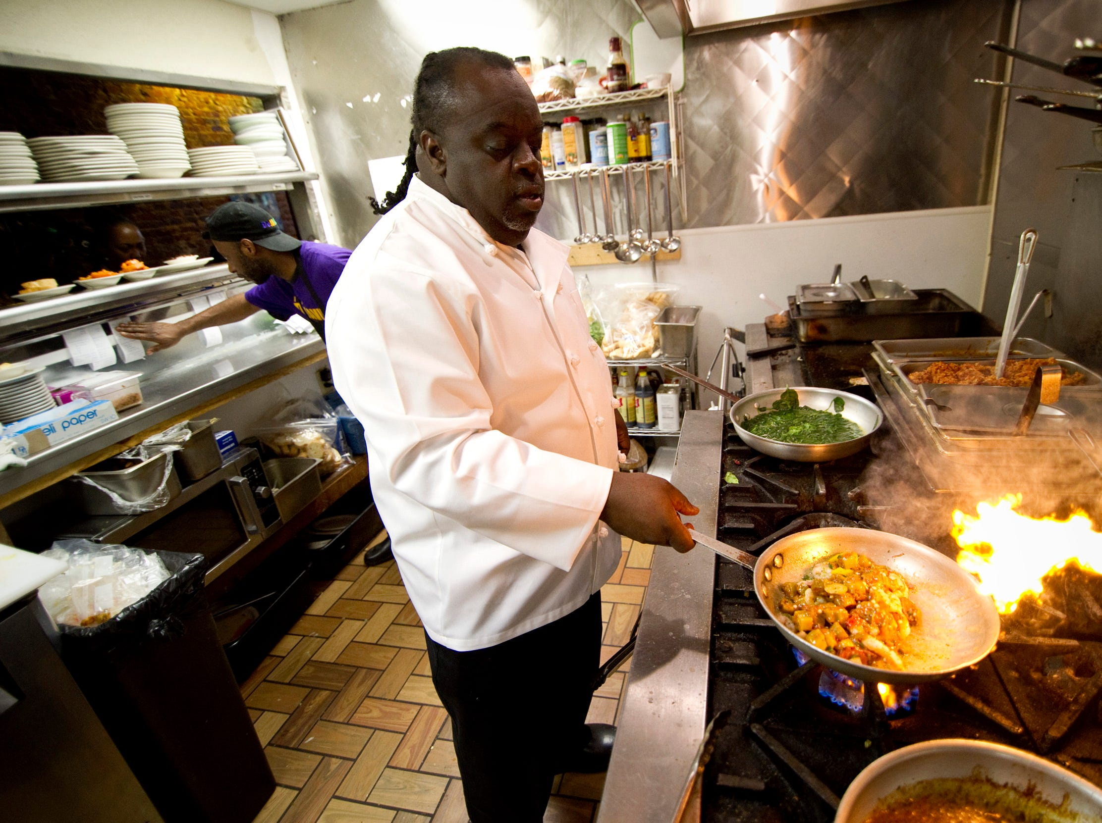 "Feb 21, 2014 - DejaVu Chef Gary Williams cooks an order of ""Toni's Voodoo Roux"" during lunch at his restaurant's downtown location on South Main St."
