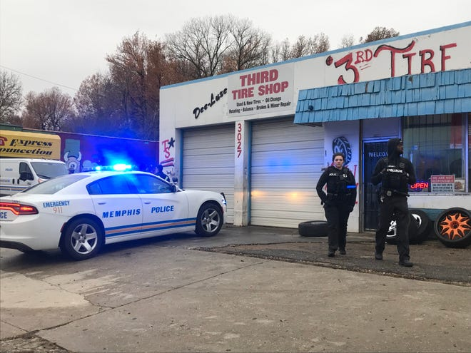 Cops sit outside of Third Tires Shop in Southwest Memphis where two men were shot and killed Thursday.