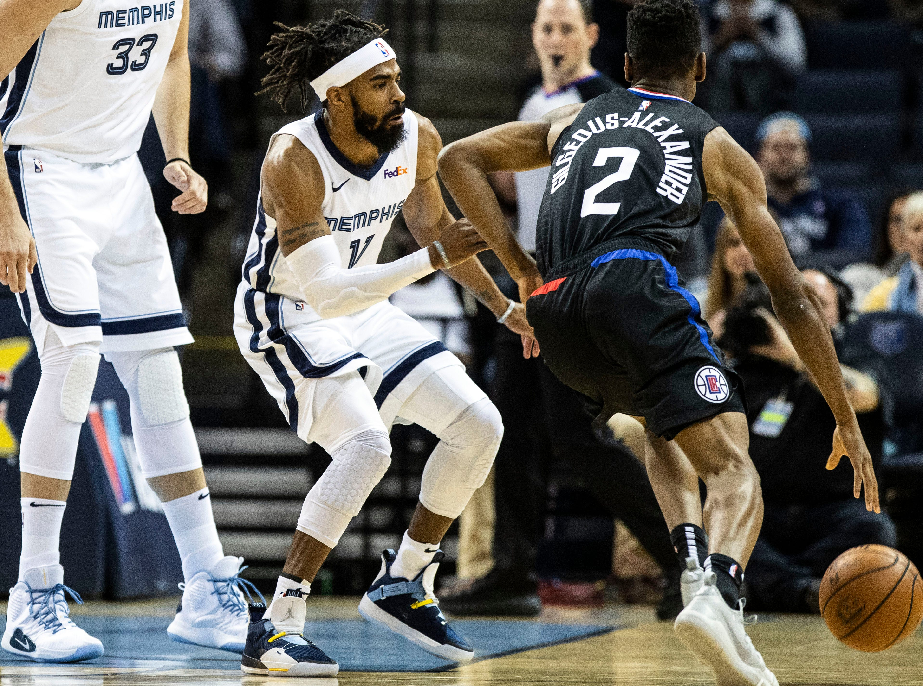 Memphis Grizzles guard Mike Conley (11) blocks Los Angeles Clippers guard Shai Gilgeous-Alexander (2) during a NBA basketball game in the Fedex Forum, Wednesday, Dec. 5, 2015.