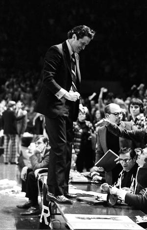 Marquette coach Al McGuire stands on top of the scorers table after his team beat Wisconsin, 59-58, at the Milwaukee Arena on Feb. 5, 1974.