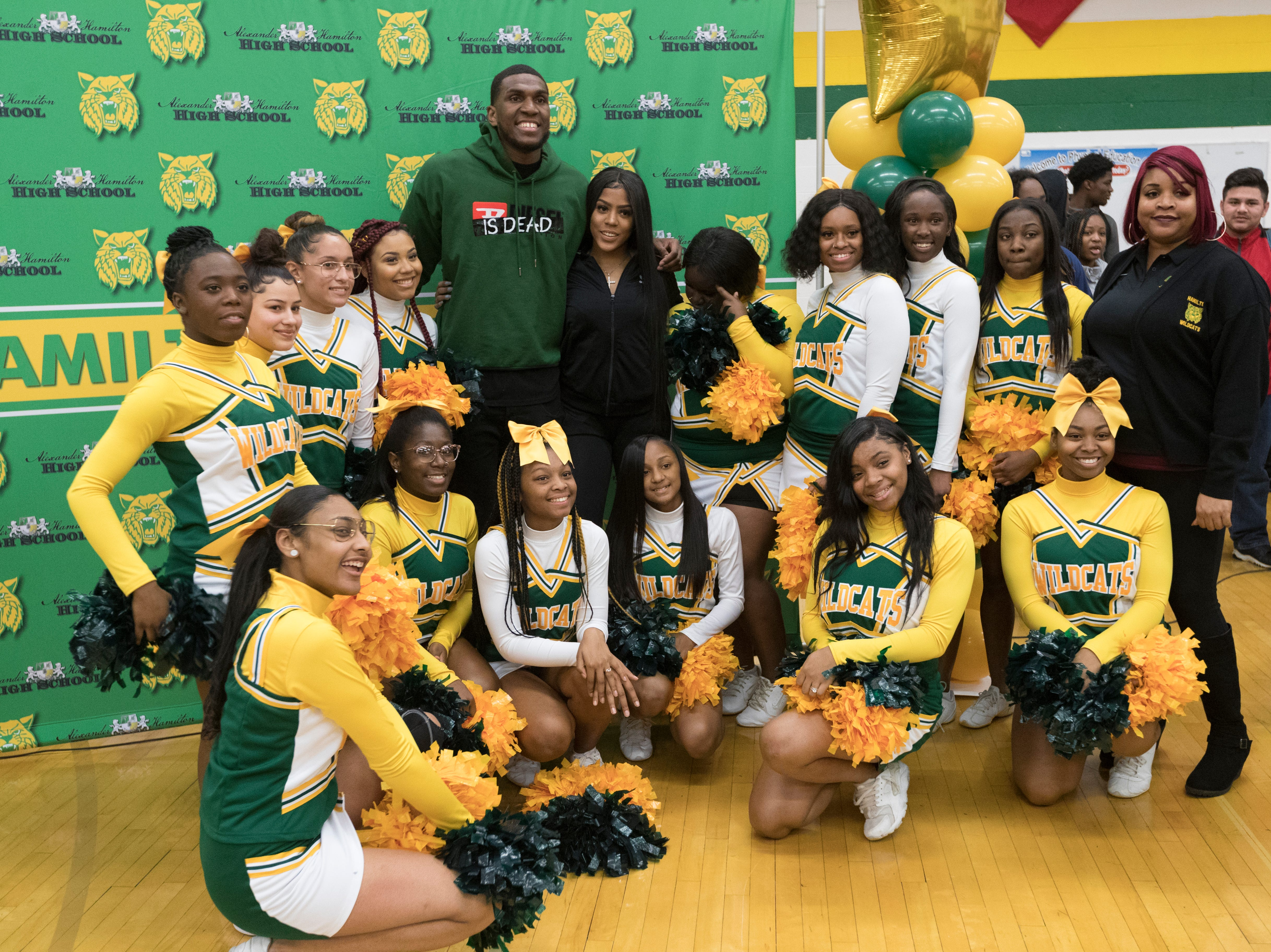 Golden State Warrior center Kevon Looney poses with high school cheerleaders while taking part in a ceremony where his jersey is retired  Thursday, December 6, 2018 at Hamilton High School.