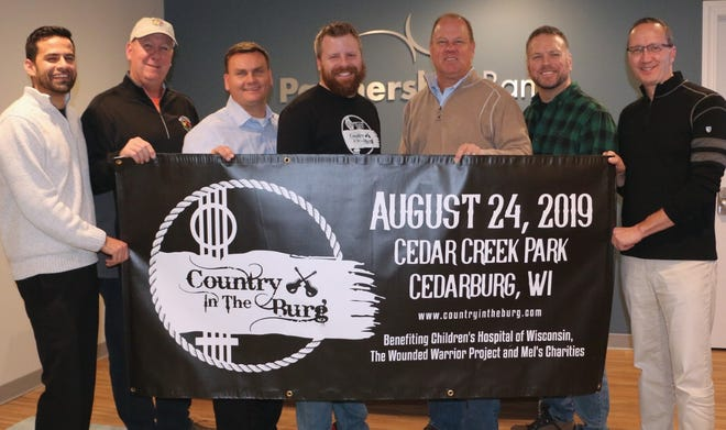 (From left) Partnership Bank assistant vice president of business development Rahim Keval, Mel's Charities executive director Tom Stanton, Cedarburg parks recreation and forestry director Mikko Hilvo, Country in the Burg founder, organizer and promoter Alex Uhan, Country in the Burg promoter Randy Groth, Cedarburg mayor Michael O'Keefe and Partnership Bank CEO David Braaten celebrate Country in the Burg.
