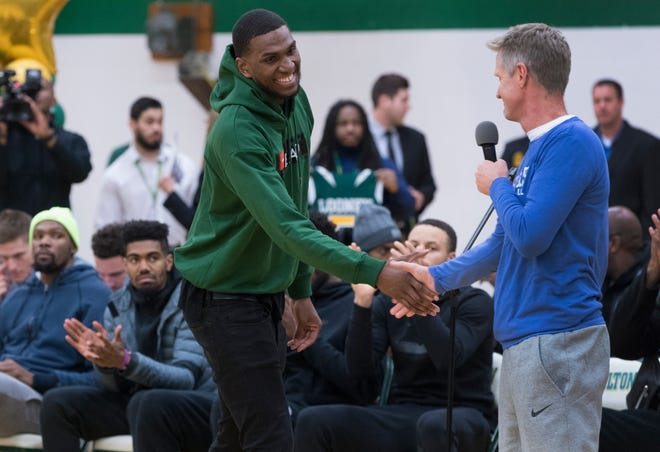 Golden State Warrior center Kevon Looney (left) is introduced by his current head coach, Steve Kerr,while taking part in a ceremony where his jersey is retired  Thursday, December 6, 2018 at Hamilton High School.