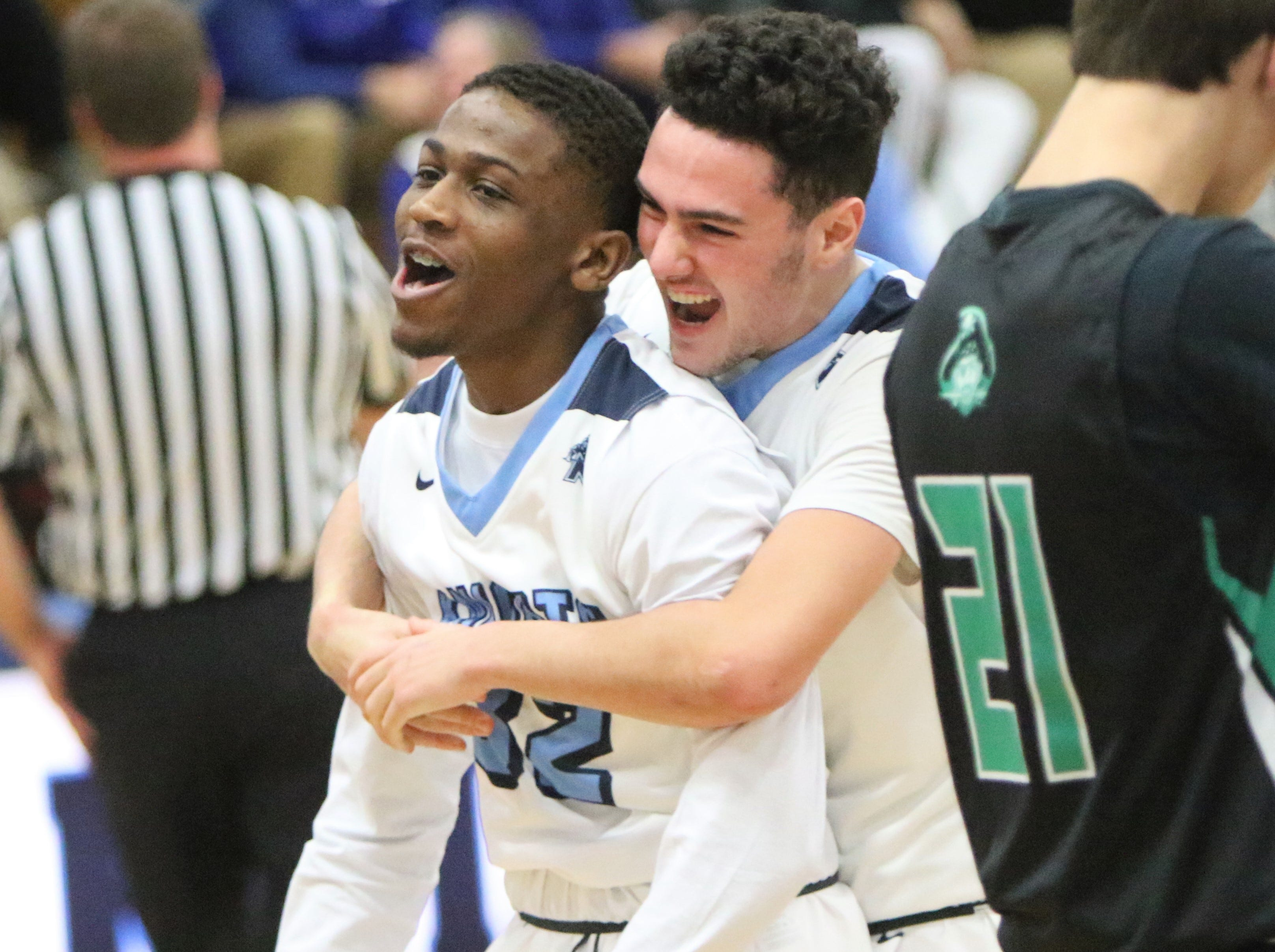 Nicolet's David Rosengarten (back) hugs teammate Jwayne Gordon after Gordon scored through a foul against Port Washington on Wednesday, Dec. 5.