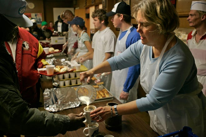 Ginny Schrag pitches in to help serve breakfast at The Gathering, a soup kitchen she runs at St. James Episcopal Church in this 2004 file photo. Volunteering at soup kitchens, or elsewhere, is beneficial year-round.