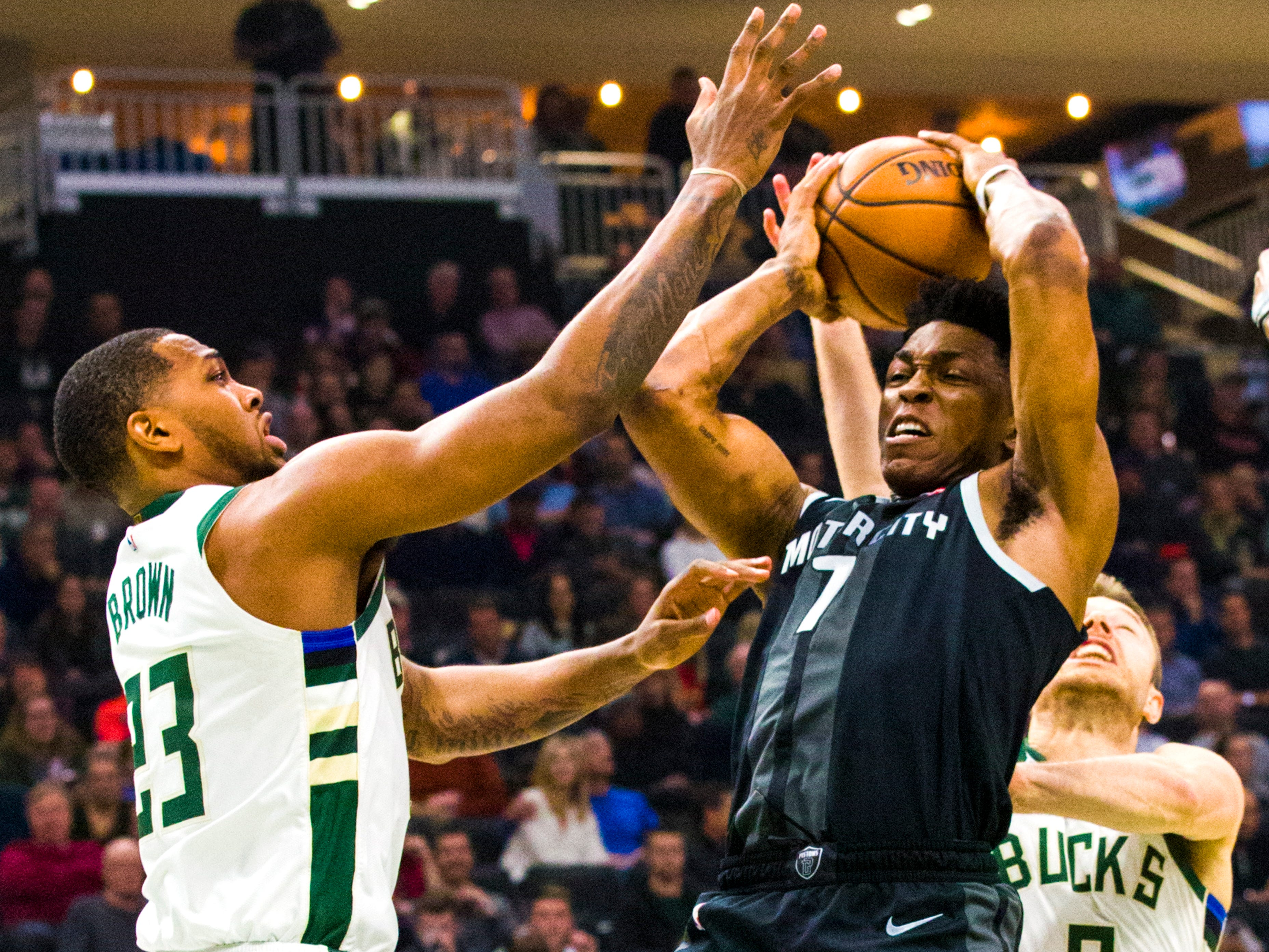 Pistons forward Stanley Johnson battles for a rebound against Sterling Brown (left) and Matthew Dellavedova of the Bucks on Monday night.