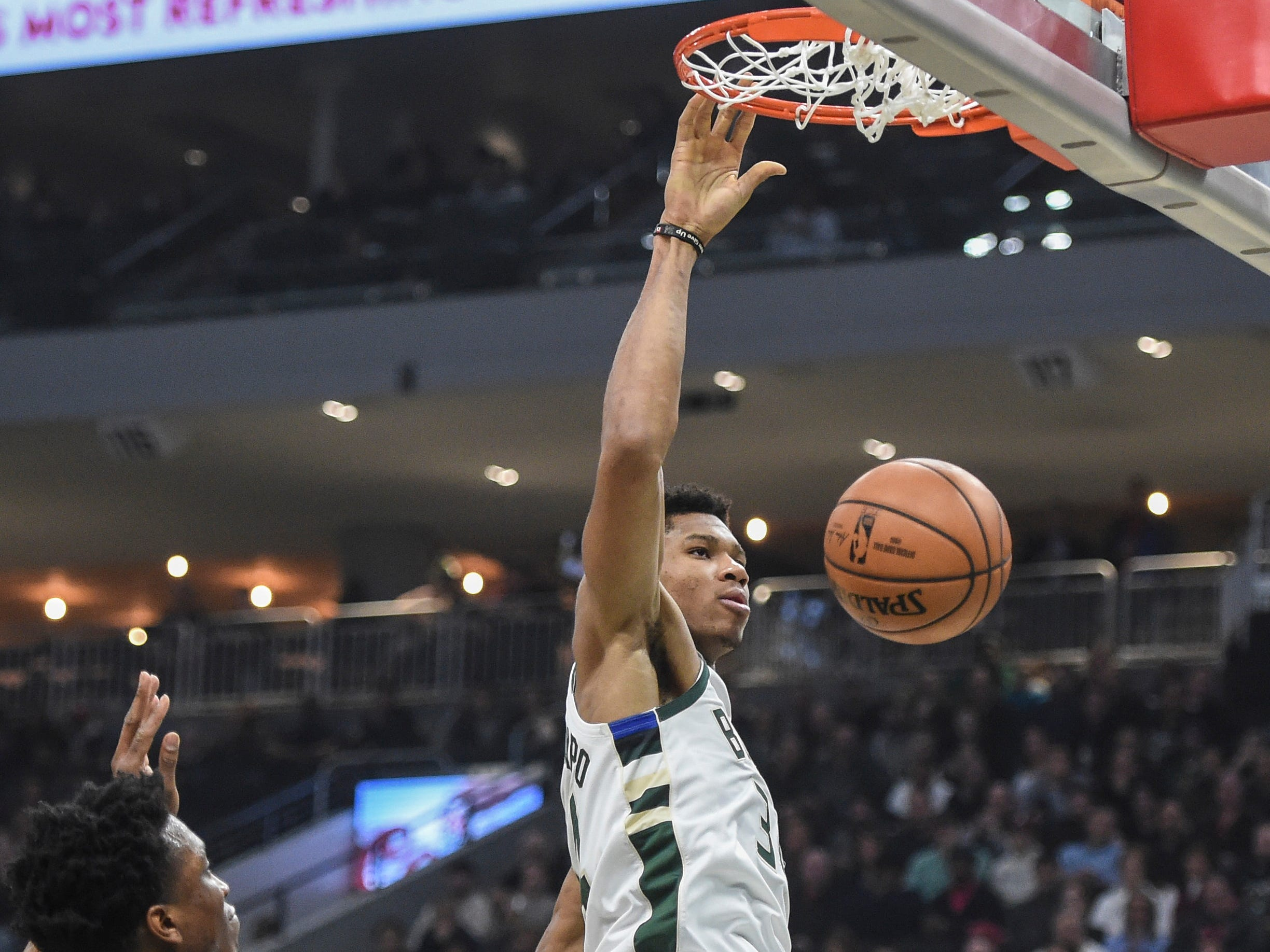 Bucks forward Giannis Antetokounmpo finishes off a dunk between Stanley Johnson and center Andre Drummond of the Pistons on Wednesday night.