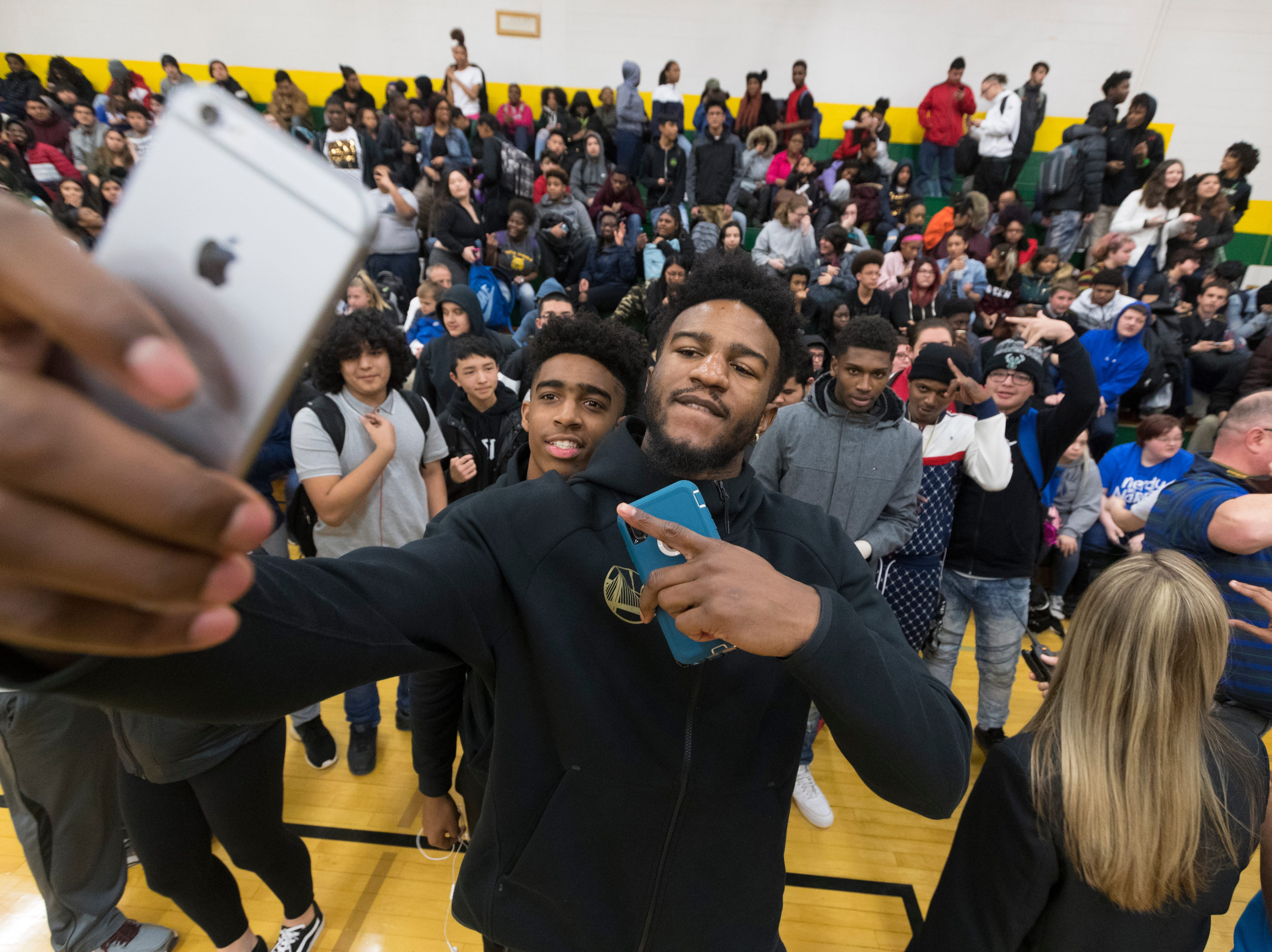 Golden State Warrior forward Jordan Bell takes a selfie with student William Lee while his teammate center Kevon Looney takes part in a ceremony where his jersey is retired  Thursday, December 6, 2018 at Hamilton High School.