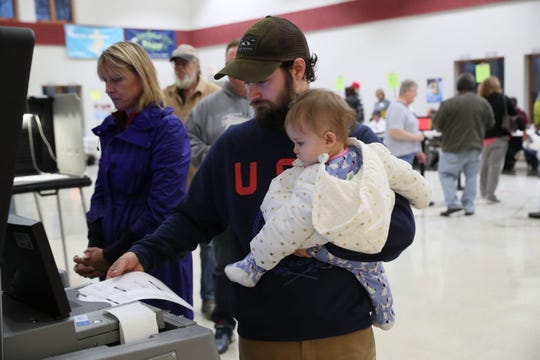 Tyler Been holds his 10-month-old daughter, Margaret Been, as he feeds his ballot into a machine to be read during the November midterm election. Political campaigns and parties are frequently searching for volunteers.