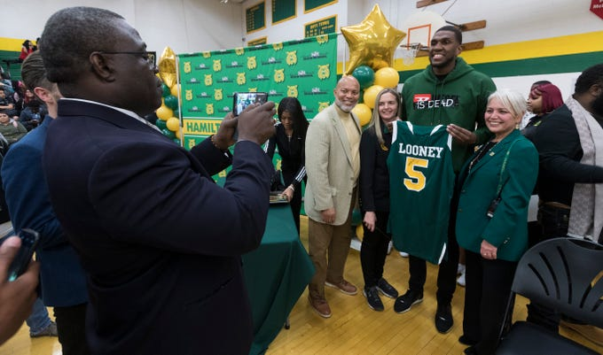 Golden State Warrior center Kevon Looney poses for photos with principal Rose Martin (right) and others while taking part in a ceremony where his jersey is retired  Thursday, December 6, 2018 at Hamilton High School.
