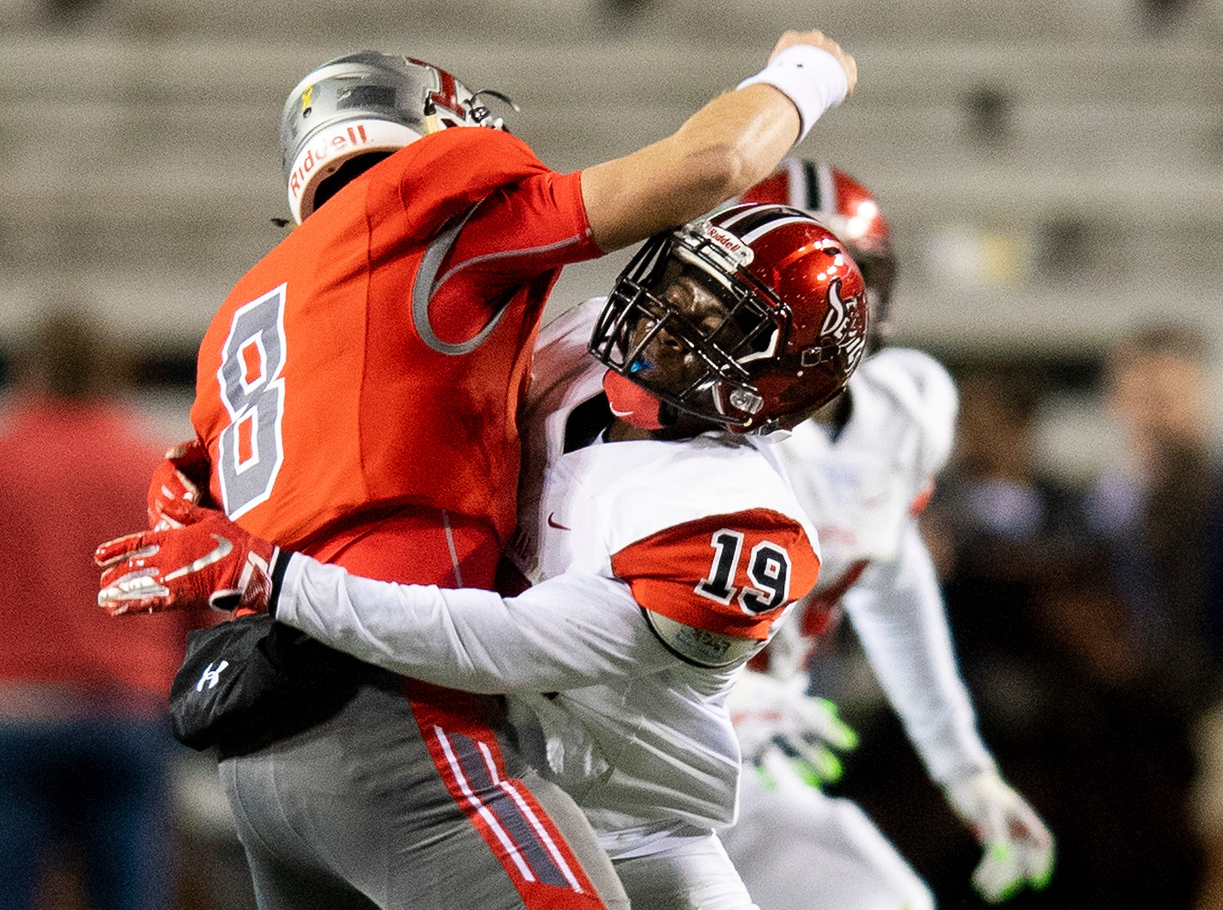 Central-Phenix City's Terrell Covington hits Thompson's Sawyer Pate as he releases his pass during the AHSAA Class 7A State Championship Football Game at Jordan Hare Stadium in Auburn, Ala., on Wednesday evening December 5, 2018.