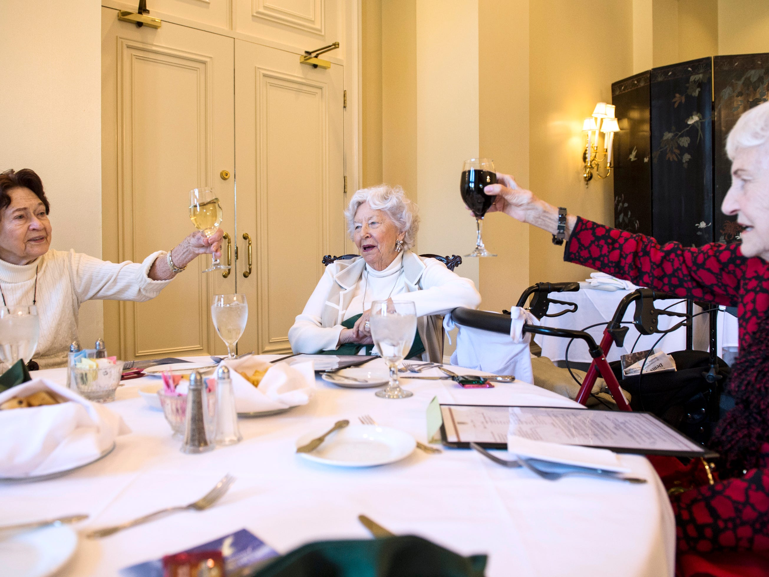 Peggy Joseph, left, and Dot Hawthorne, right, cheers during lunch at Montgomery Country Club in Montgomery, Ala., on Wednesday, Dec. 5, 2018.