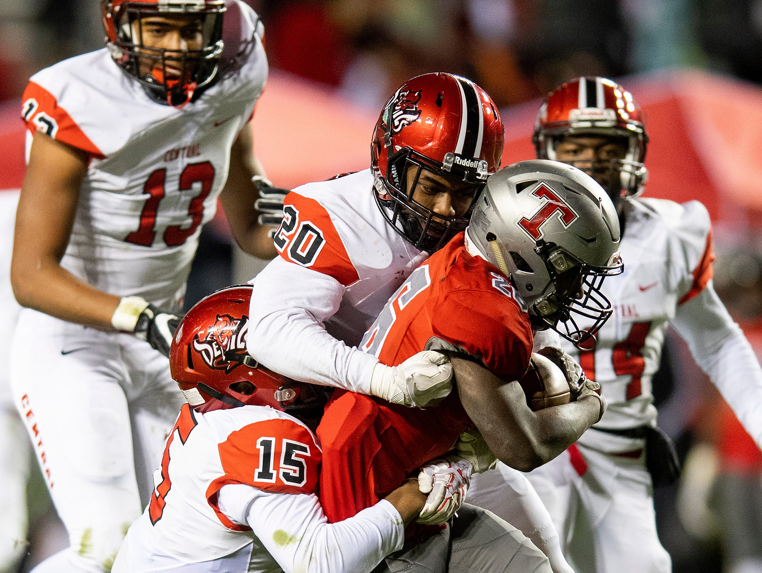 Thompson's Jarrett Crocket is stopped by Central-Phenix City's Martaveous Caple (20) and Jadon Richardson during the AHSAA Class 7A State Championship Football Game at Jordan Hare Stadium in Auburn, Ala., on Wednesday evening December 5, 2018.
