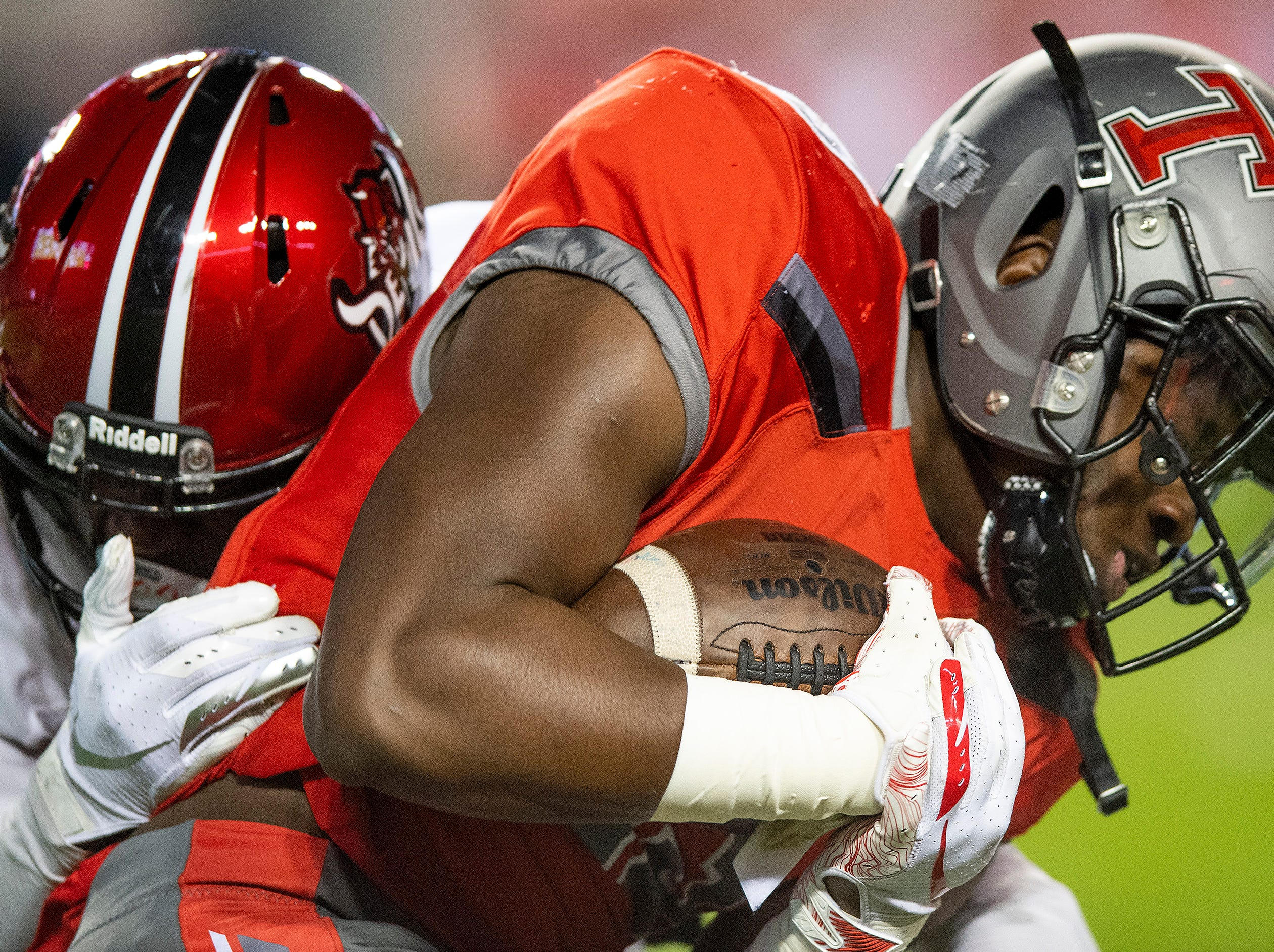 Thompson's Shadrick Byrd is stopped by Central-Phenix City's Trevon Miller during the AHSAA Class 7A State Championship Football Game at Jordan Hare Stadium in Auburn, Ala., on Wednesday evening December 5, 2018.