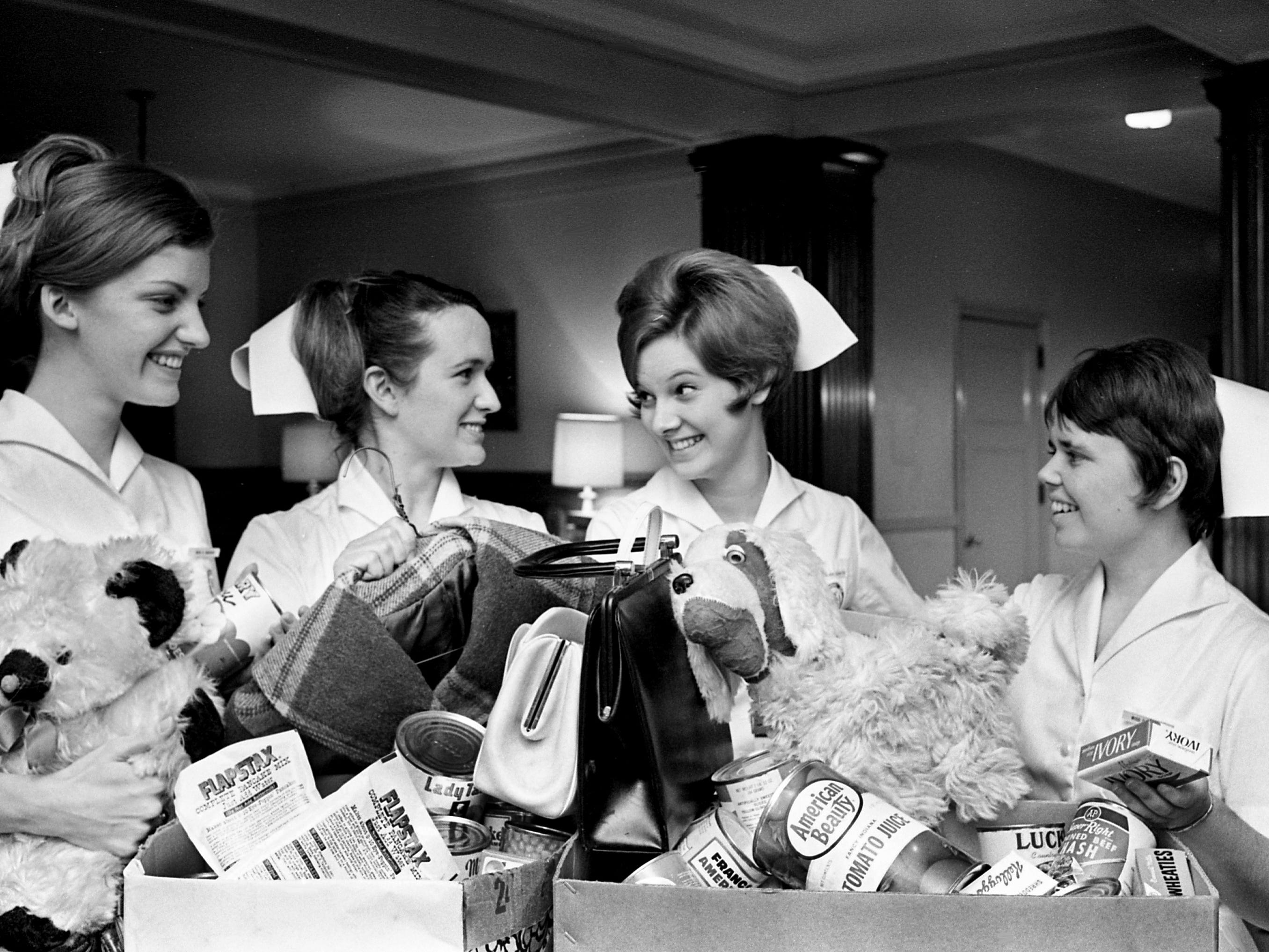 St. Thomas School of Nursing students Catherine Gregory, left, Dot Shelton, Deanie Smith and Denise Hooper, all student body officers, gather food and clothing Nov. 26, 1968 that will be given to needy families during the holiday season.