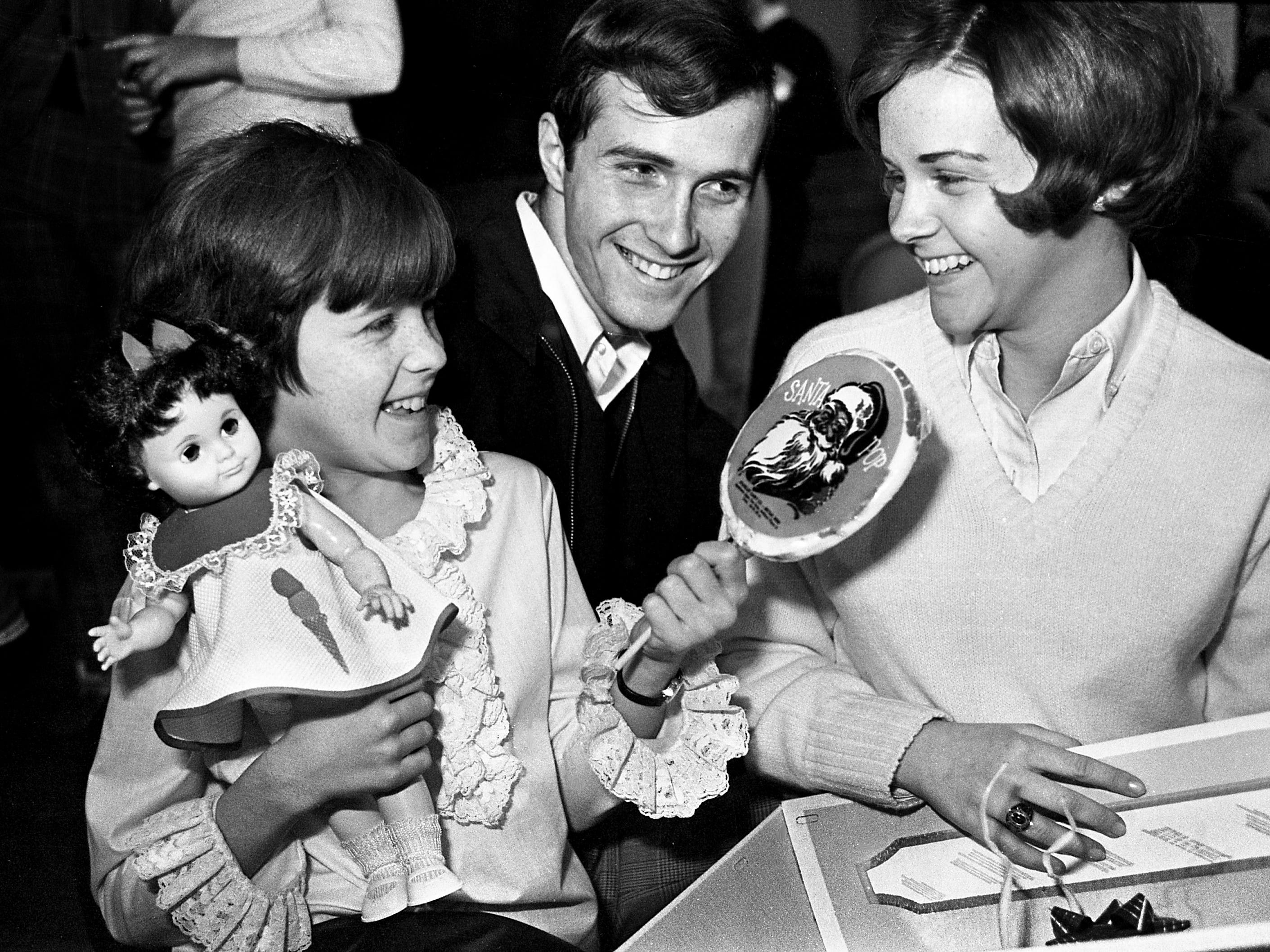Happily gripping a doll, Nancy Moore, 12, fifth grader at Tennessee Preparatory School, gets a big Christmas sucker from Billy Merritt and Carol Wilson, seniors at East High School, during a Christmas party given by three East High School clubs for TPS youngsters in the East gymnasium Dec. 17, 1968.