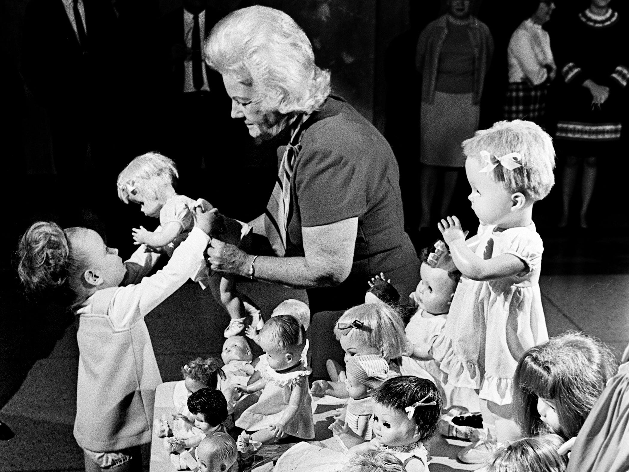 Tammy Lee Spalding, 3, admires a baby doll Nov. 15, 1968 held by Mrs. Burns Schelland, right, who dressed this doll and 21 others for the needy children of Nashville for this Christmas. The girl, daughter of Mr. and Mrs. Donald Spalding of Bonnaside Drive, drew the winning ticket out of more than 400 chances sold on a Barbie doll wardrobe to raise money for the project.