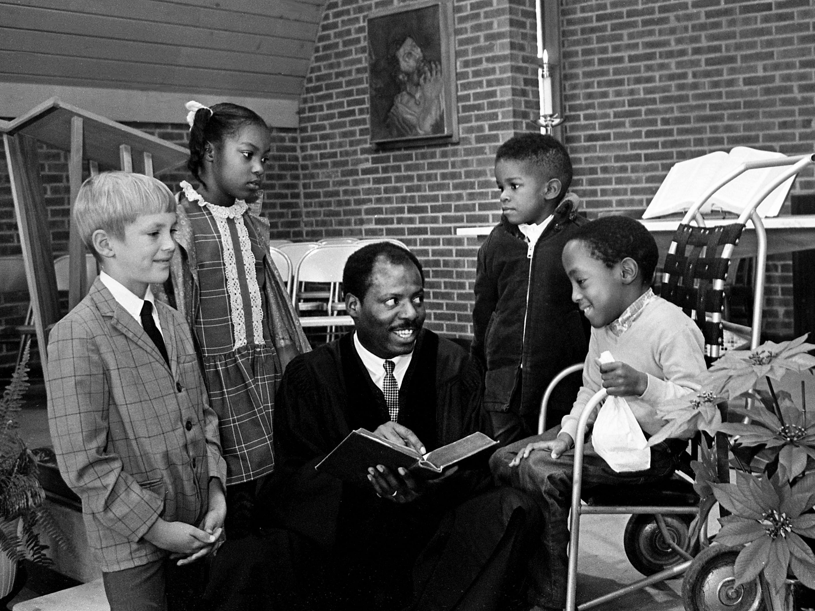 The Rev. H. Berman Taylor, center, pastor of the Howard Congregational Church (United Church of Christ), tells the Christmas story to children of the church school and children's choir Dec. 22, 1968. Listeners are Brooks Egerton, left, Regina Hall, Hycel Taylor III and Keith Blakely.